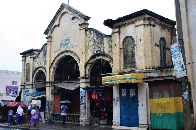 The old Ford building in old Accra on the outskirts of Makola Market, with peeling paint and an architectural style that dates back many years. It is rainy and people walk by with umbrellas.