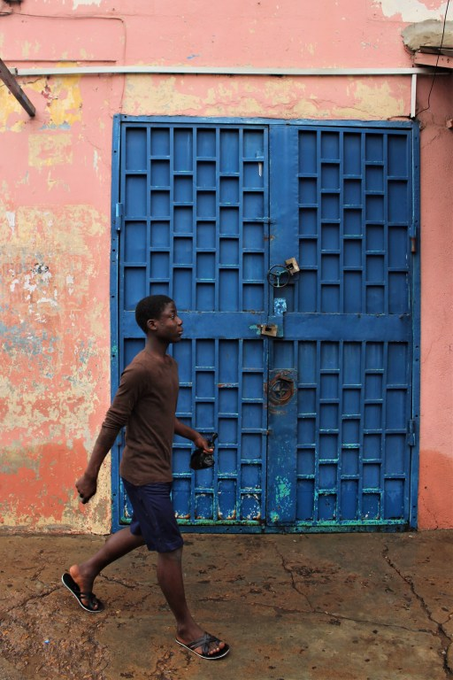 A young boy walks in front of a blue door on the outskirts of Makola Market Accra, the wall has many layers of paint that are peeling from it.