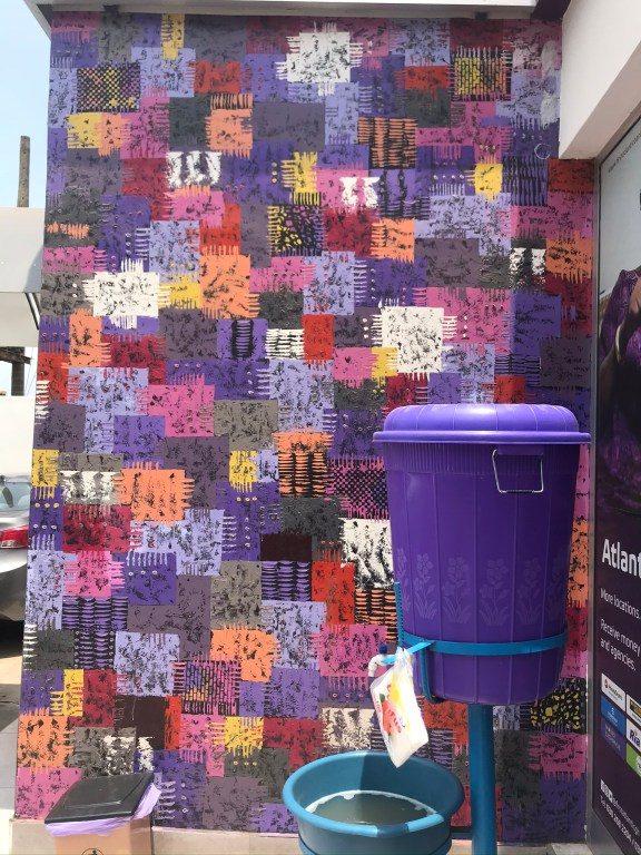 Ghana during the Corona pandemic, A veronica bucket stands in front of a wall painted like traditional Kente cloth
