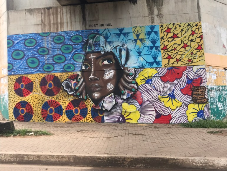 A street mural in Airport area in Accra Ghana of a lady pulling herself through African wax fabric.