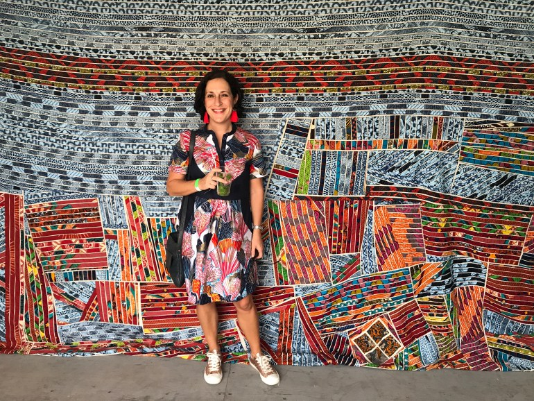 BloBlogger Lauren Simpson stands in front of Ghanaian artist Tei Huagie's quilts made from African wax fabrics