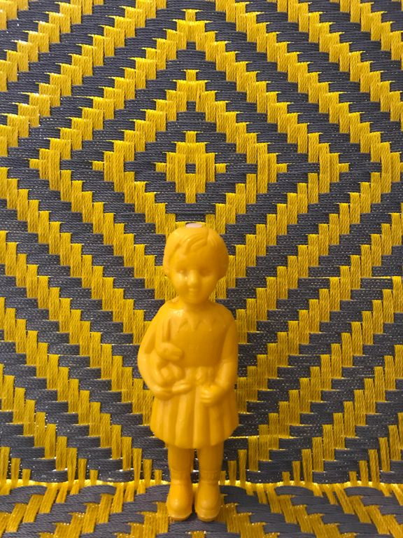 Yellow baby Clonette Doll stands against a backdrop of a yellow and grey chair woven by Joel of Calao Creations in Ghana