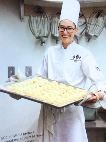 A girl in a white chef's outfit holding a tray of unbaked pastries