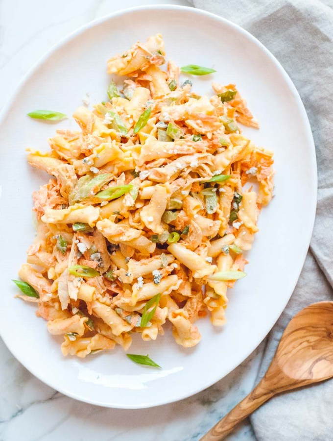 buffalo chicken pasta salad on a white plate with a wooden spoon