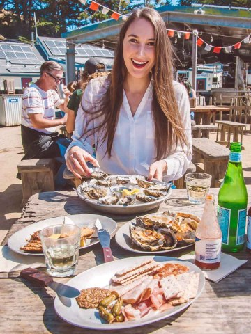 girl outside at hog island oyster co. with plates of food in front of her