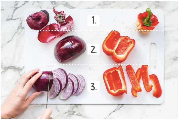Red onion and bell peppers laid out on a white cutting board to demonstrate the three steps of cutting veggies into thin strips.