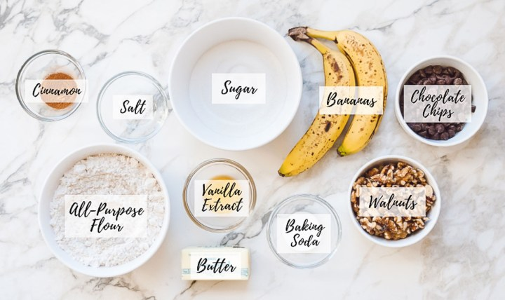 Overhead image of all ingredients needed for this recipe portioned out in their appropriate measurements with text overlay labeling each ingredients, including cinnamon, all-purpose flour, salt, butter, vanilla extract, sugar, two bananas, baking soda, walnuts, and chocolate chips.