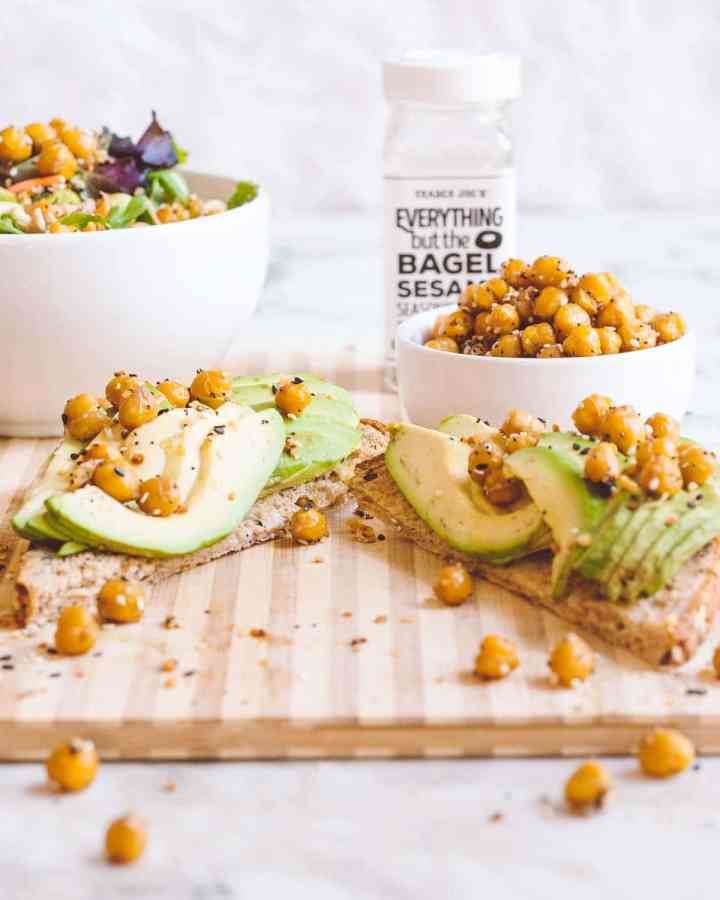 Cut avocado toast on a wood board with chickpeas tossed around with a white bowl of salad and empty glass bottle of seasoning in the background.