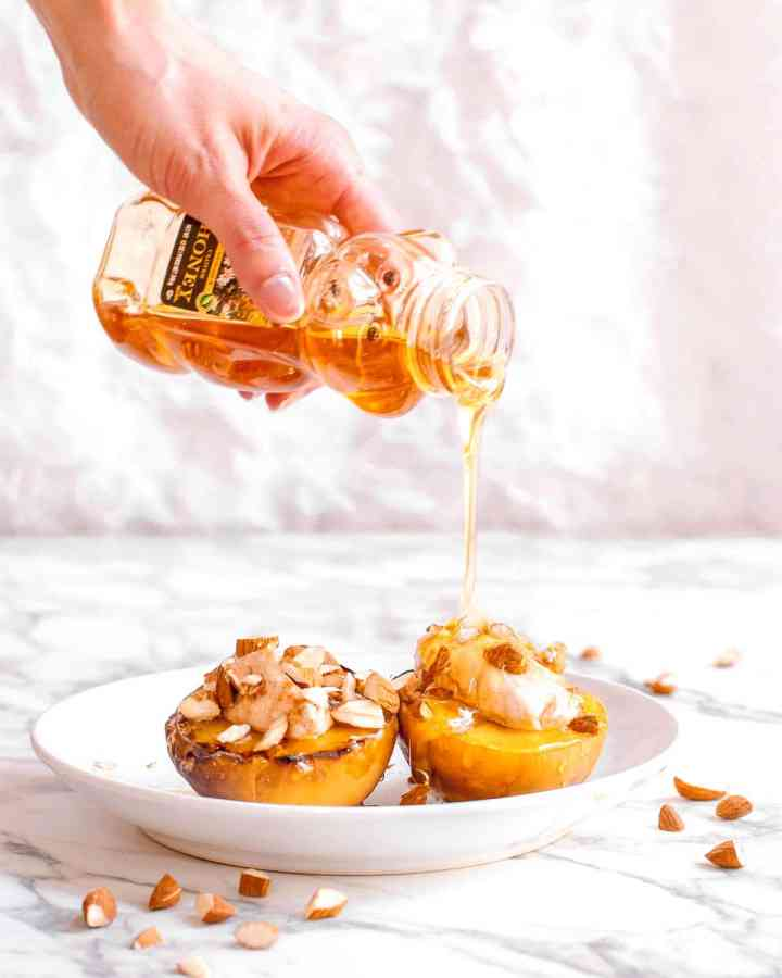 A hand is reaching over the top of the image and drizzling a jar of honey over two peach halves that have been roasted and topped with almonds and mascarpone cheese and are placed on a white plate.