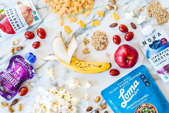 Snack foods like a peeled banana, red apple, cherry tomatoes, a baggie of gold fish crackers, a baggie of pop corn, crackers, and squeezable fruit puree all laid about on a white tile.