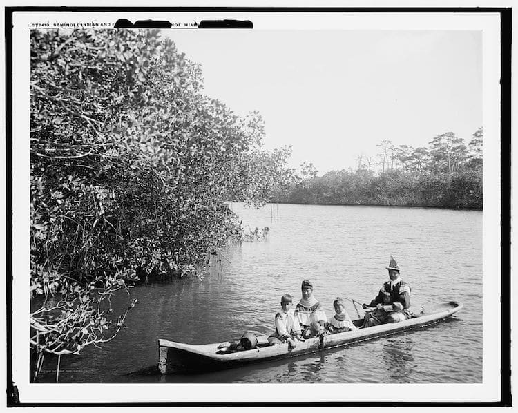 Seminole Indian and family dugout canoe, Miami, Fla.