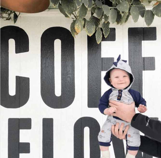 baby in front of coffee and flowers sign