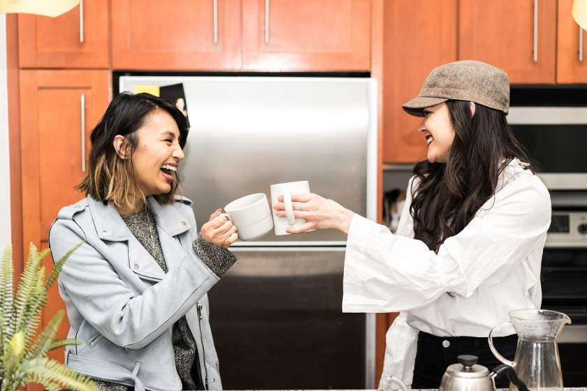 girls doing cheers with coffee cups in kitchen