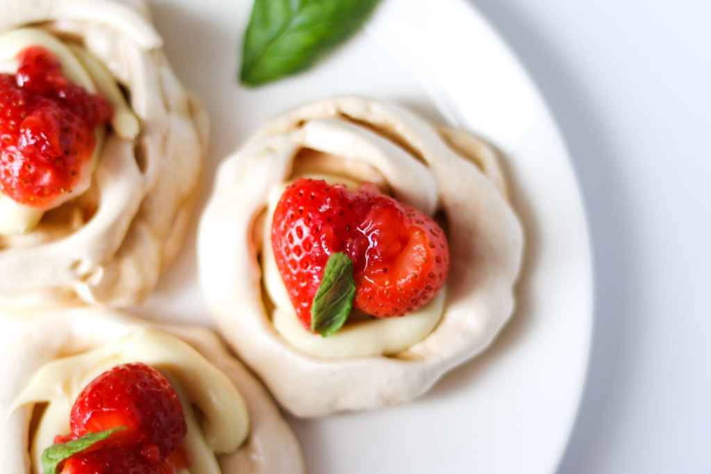 A plate with homemade meringue nests filled with a delicious pavlova filling with white chocolate ganache.