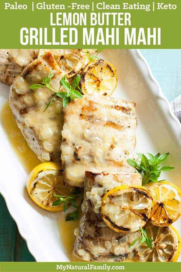 Grilled Mahi Mahi recipe with a lemon butter sauce with sliced lemons on top on a white plate with a turquoise background and a white and blue napkin on the side