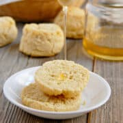 Light and Fluffy Paleo biscuits on a white plate with honey being drizzled on top on a wood table with a jar of honey in the background