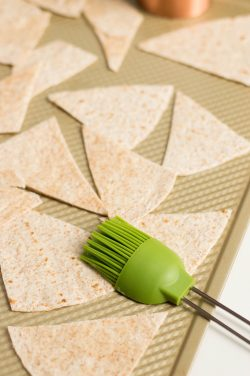 Place tortilla triangles on baking sheet and brush with oil