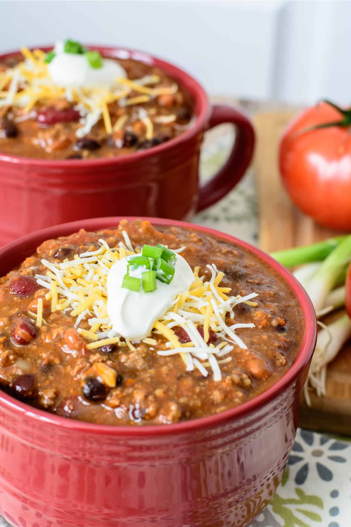 Quick and easy chili from scratch topped with sour cream, cheese and green onion.