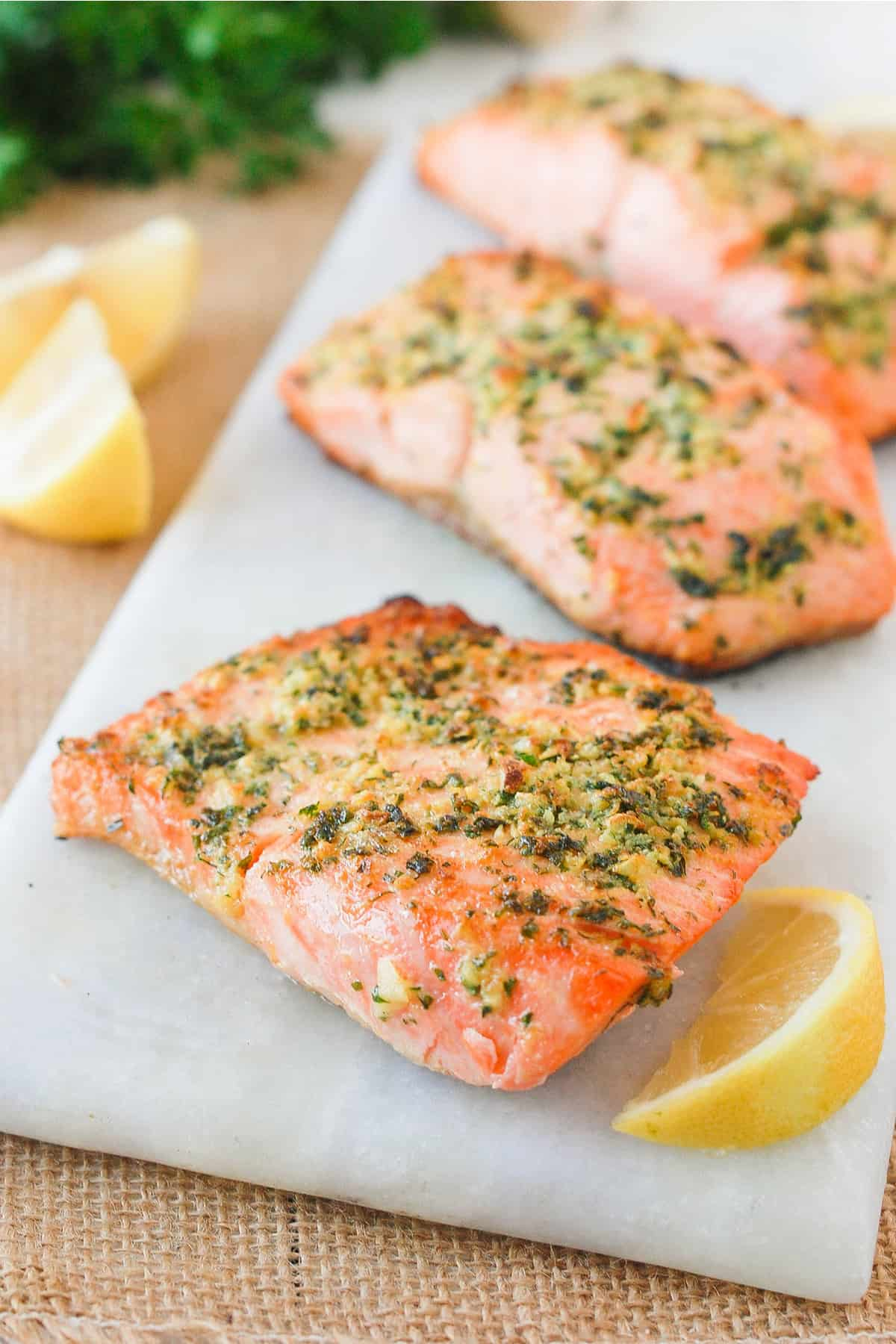 Herb baked salmon with lemon and garlic on a white cutting board.