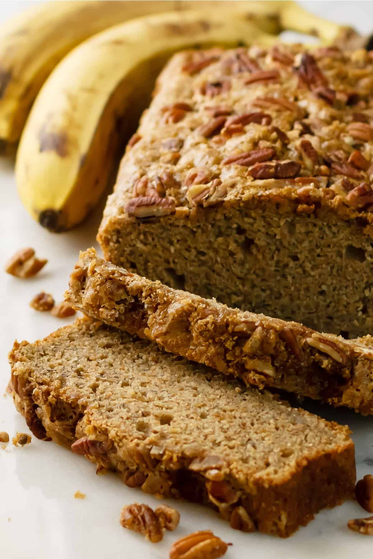 Dairy-free banana bread recipe sliced with ripe bananas in the background on a white table.