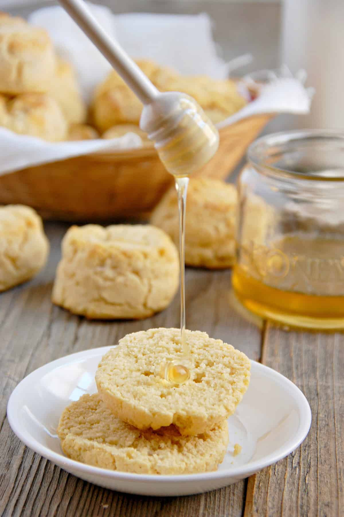 Fluffy Paleo biscuits on a small white plate with honey being drizzled on them and some behind in a basket and a small jar of honey in the background.
