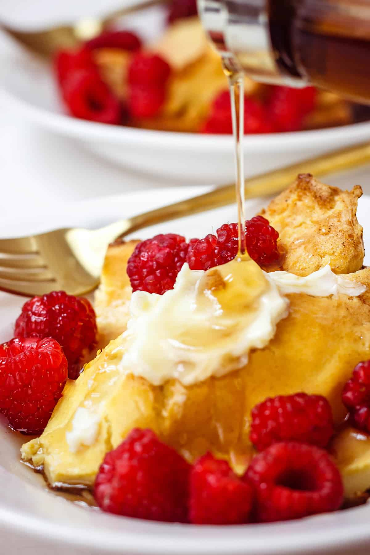 Gluten-free German pancakes on a white plate with raspberries and butter on top and maple syrup being drizzled on top.