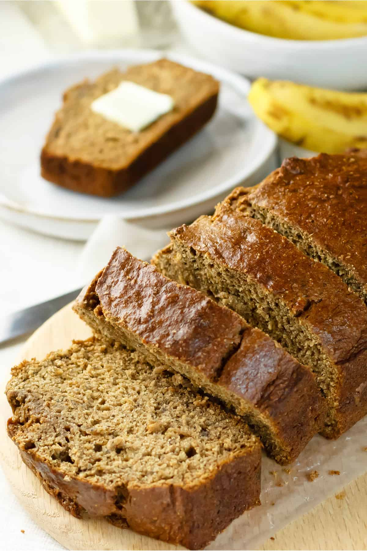 Healthy banana bread with applesauce on a cutting board sliced with a slice in the background with butter on top on a white plate and ripe bananas in the background