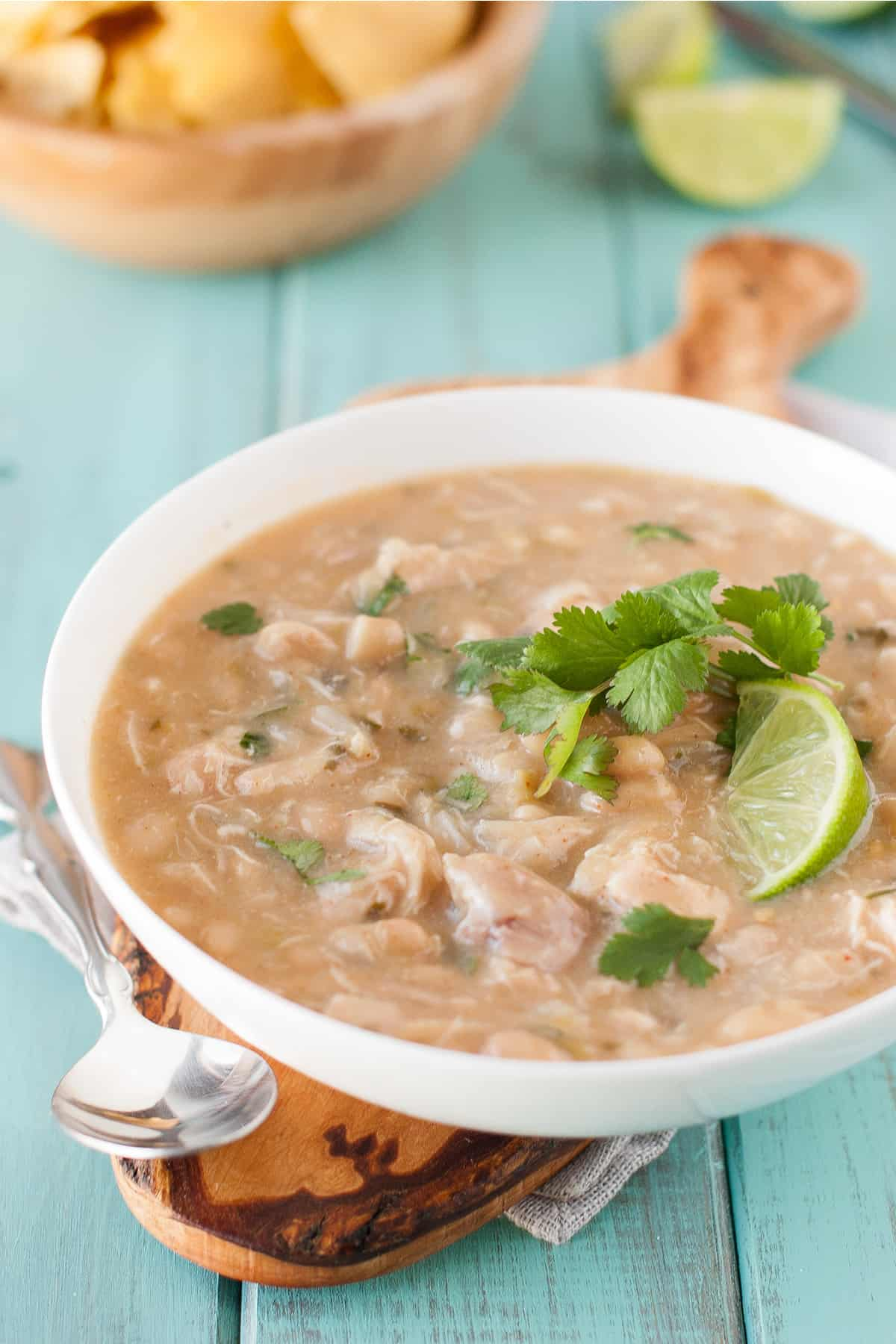 Healthy white chicken chili in a white bowl on a green background on a brown cutting board with a spoon, topped with lime and cilantro.