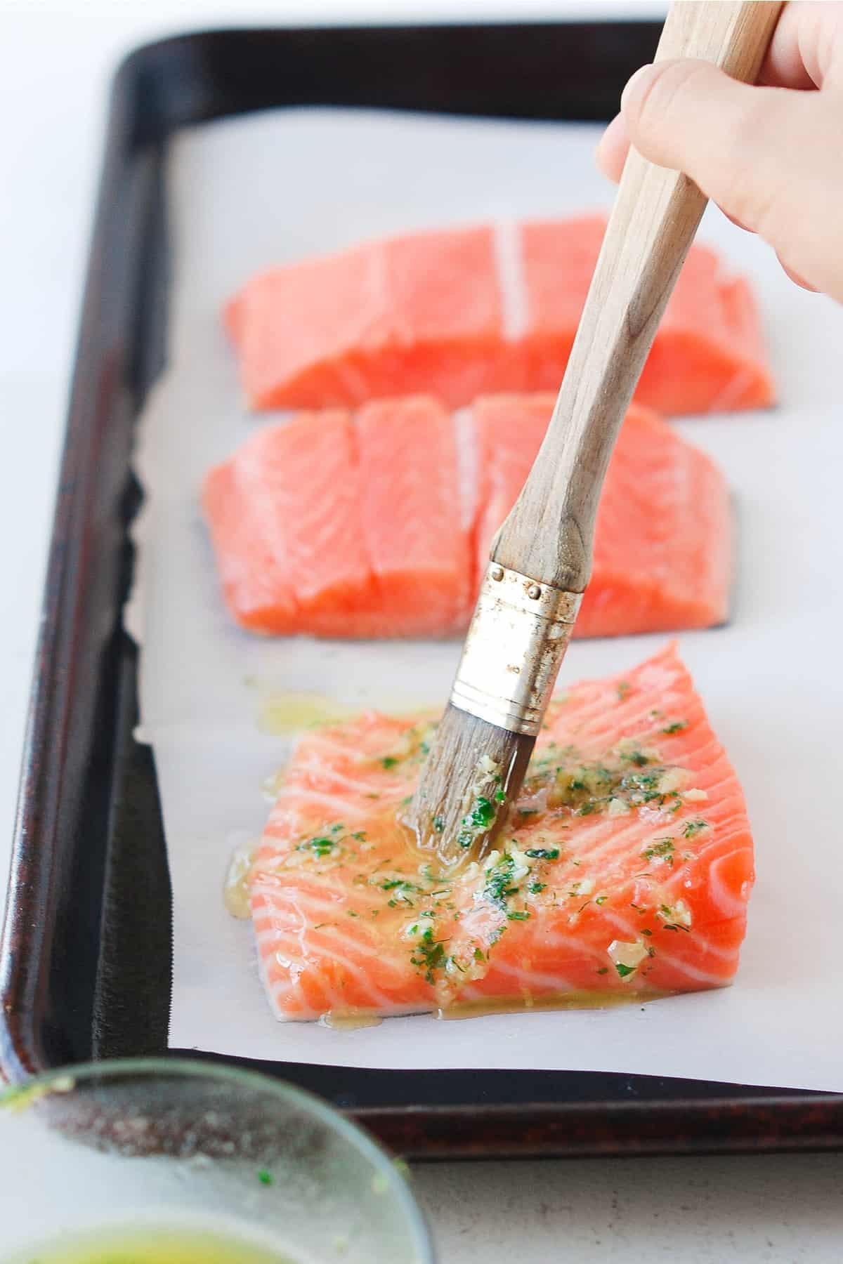 whole30 salmon brushing the lemon herb sauce on