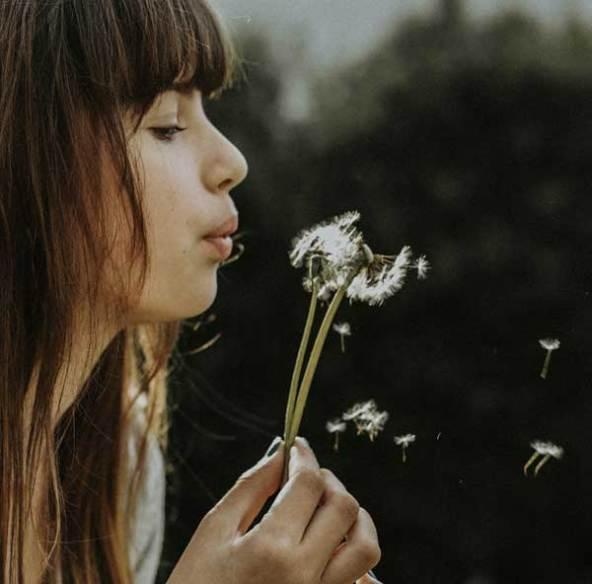 Woman enjoying relaxing by blowing dandelions