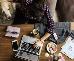Woman Using Laptop Shopping Online and Petting Dog