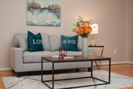 Picture of a staed family room with grey sofa and blue and orange accent colors
