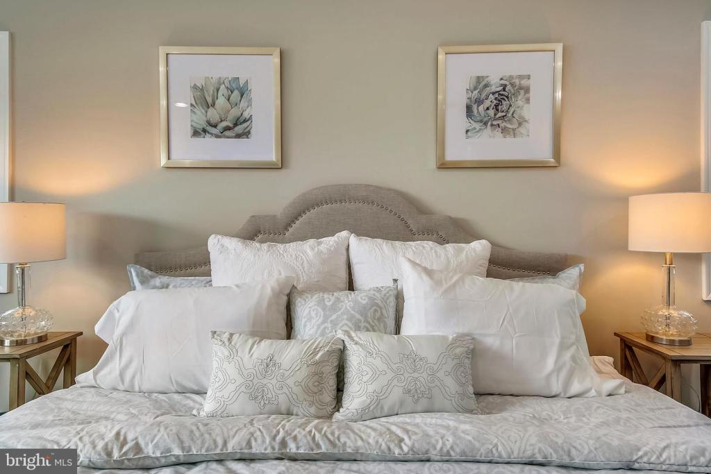 bed made with many pillows and scalloped headboard