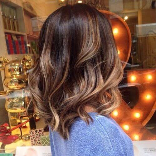 wavy lob haircut on brown hair with caramel highlights