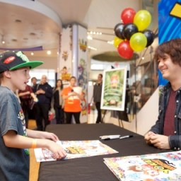 In this photo provided by Nintendo of America, Founder, President/CEO of LEVEL-5 Inc. Akihiro Hino signs autographs and poses for pictures with fans at the launch of the YO-KAI WATCH video game for the Nintendo 3DS family of systems at Nintendo World in New York on Nov. 7, 2015.