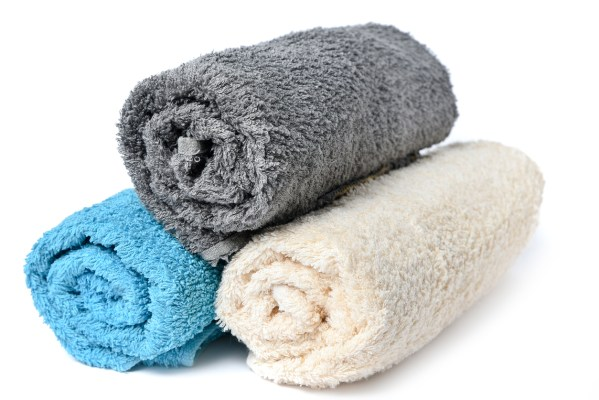 Stack of clean multi-colored towels on a white background