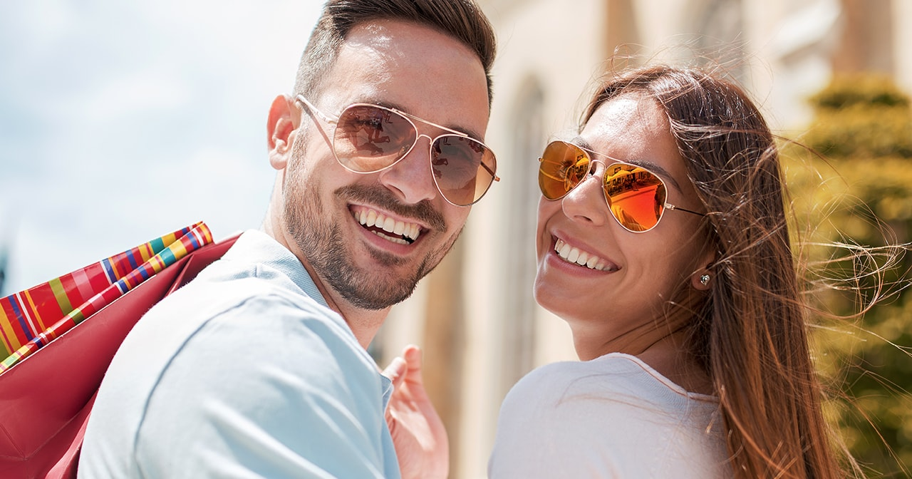 couple with sunglasses and shopping bag
