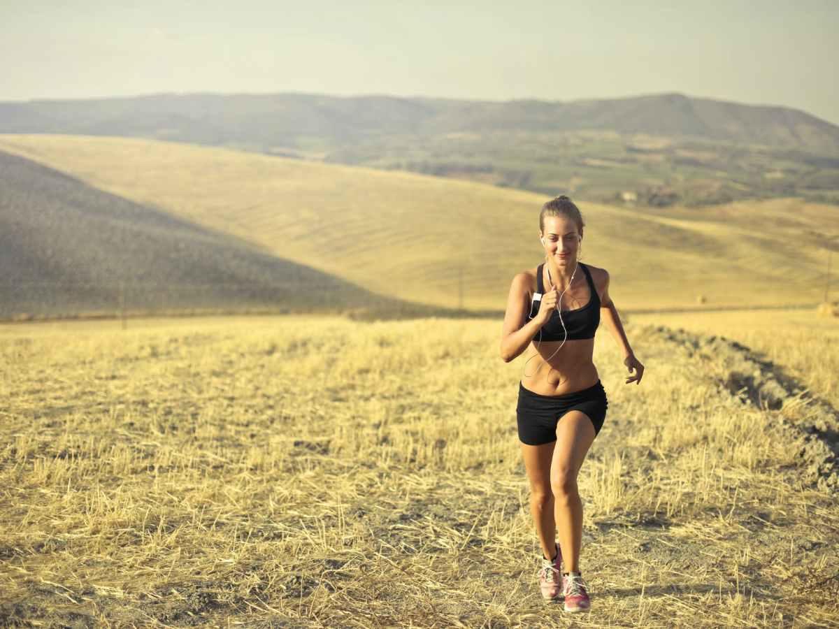 cheerful sportswoman running along hill in summer