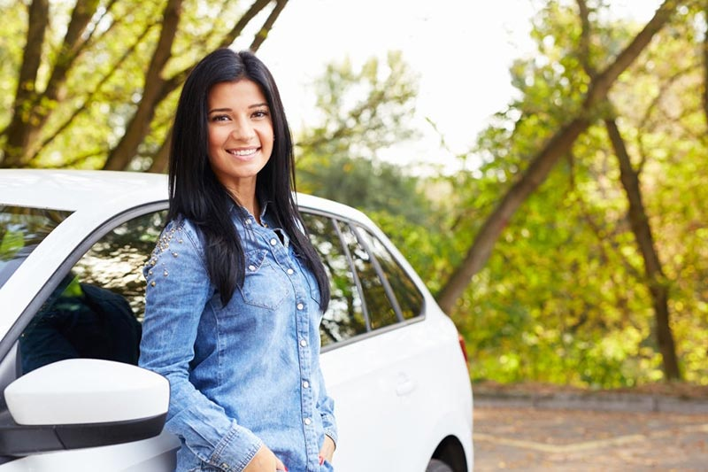 Young happy woman standing by her car in recreational travel trip