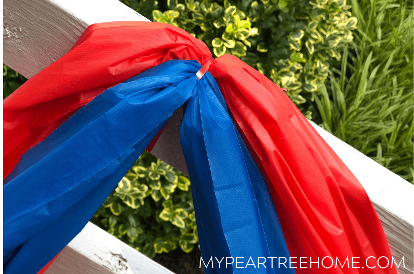 Tutorial for making bunting for 4th of July decor. Image shows two table cloths tied to porch rail with gift wrap ribbon.