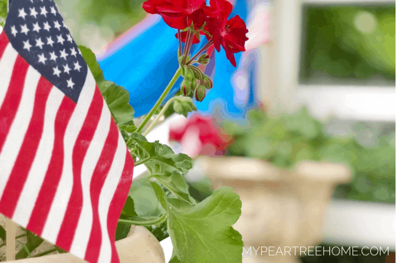 Image of American flag and geraniums. Tutorial to show how to make your own bunting for your porch for july 4th decor.