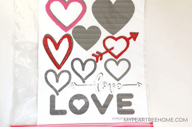 Want to learn how to make these easy window clings using puffy paint? See how simple it is and snag the free printable heart template page.