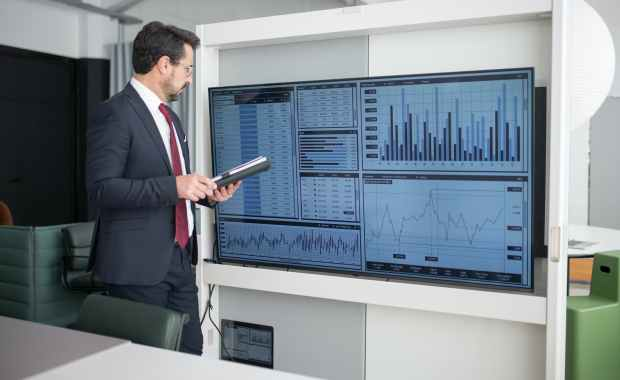 man in corporate attire looking at a wide screen monitor