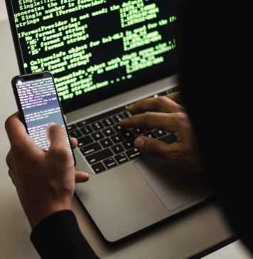 unrecognizable hacker with smartphone typing on laptop at desk