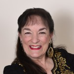 Head shot of Nancy Wyatt dressed in black with gold trim ready to teach meditation