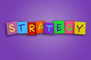 The word STRATEGY written on sticky notes on a background of purple colored paper. Strategy is for classes in a training venue.