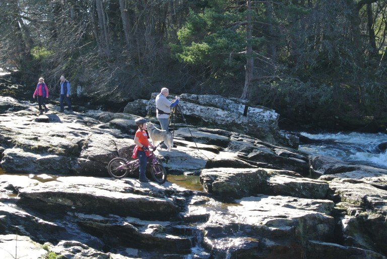 A boy on a bicycle and a man with a camera tripod on some rocks.