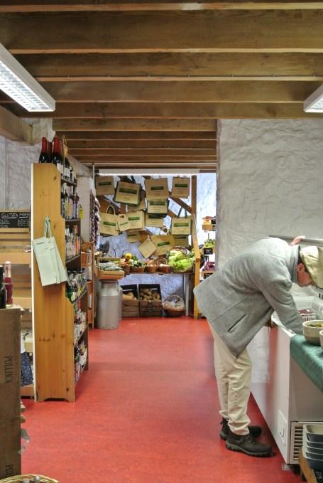 A man digging in a freezer in a farm shop.