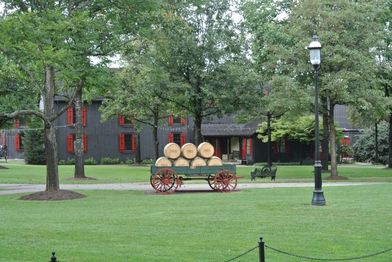 Whiskey barrels in a wagon and a gray building with red shutters.