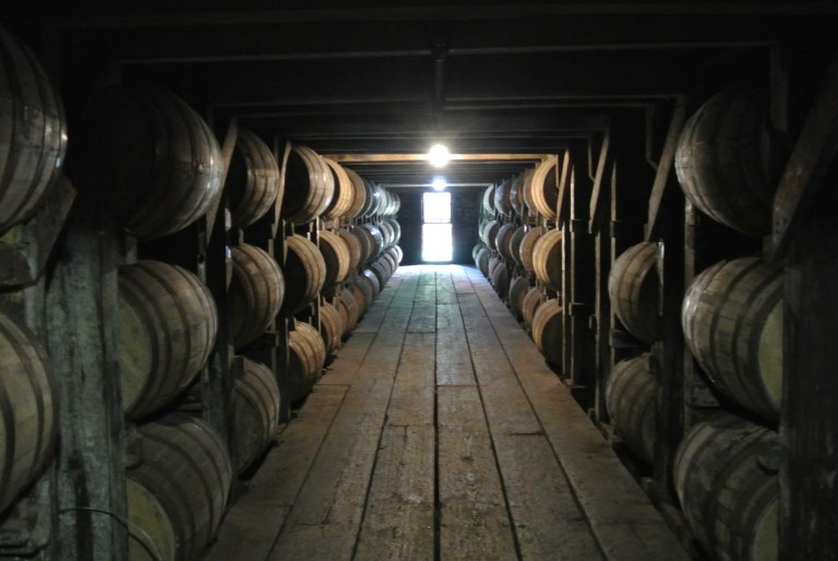 Stacked whiskey barrels in a warehouse.